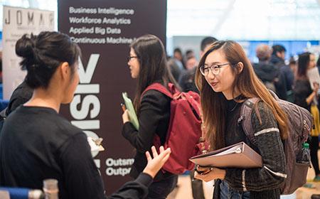 A student meets an employer at a career fair